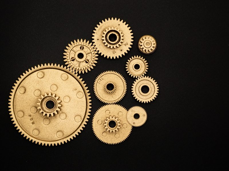 photo-of-golden-cogwheel-on-black-background-3785926 (1)